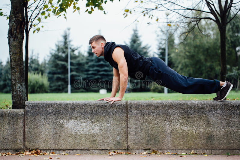 Ο αρσενικός δρομέας που κάνει την άσκηση, workout το φθινόπωρο σταθμεύει Ώθηση UPS με τον πάγκο στοκ εικόνα με δικαίωμα ελεύθερης χρήσης