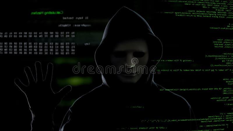 Ο αρσενικός χάκερ στο σκοτεινό υπόβαθρο αρχίζει τη διαδικασία χάραξης, stealing πληροφορίες στοκ εικόνες