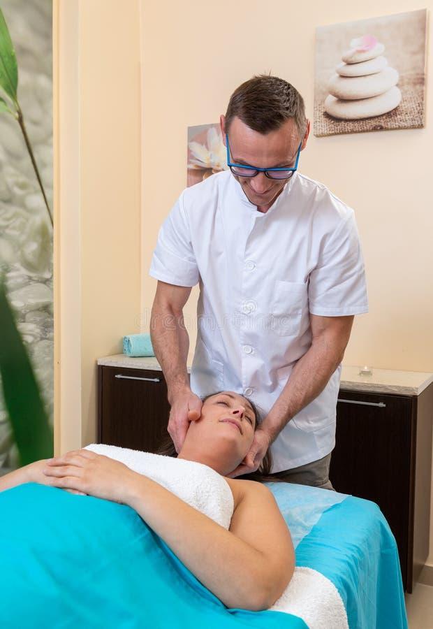 Ο αρσενικός osteopath θεράπων τρίβει το λαιμό του ασθενή, μετά από τον τραυματισμό στοκ εικόνες