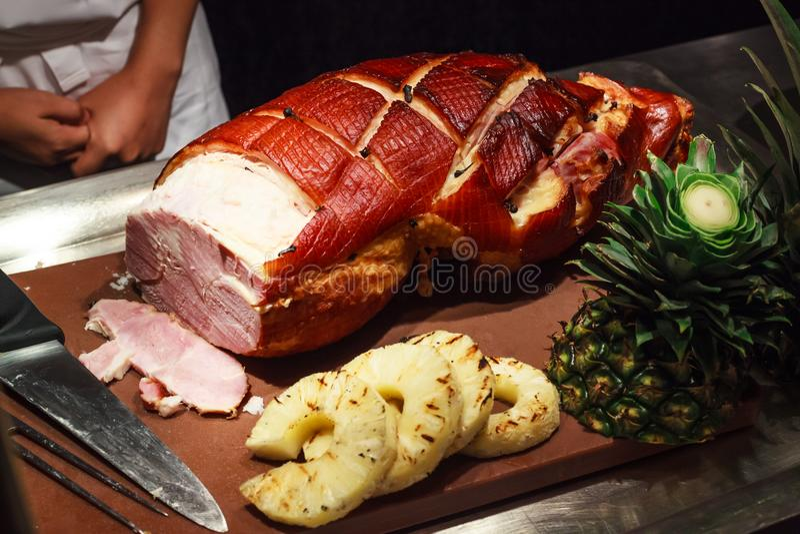 Ο αρχιμάγειρας έτοιμος να τεμαχίσει το μέλι βερνίκωσε το ψημένο χοιρινό κρέας ζαμπόν για τους φιλοξενουμένους στις διακοπές, γεγο στοκ φωτογραφία