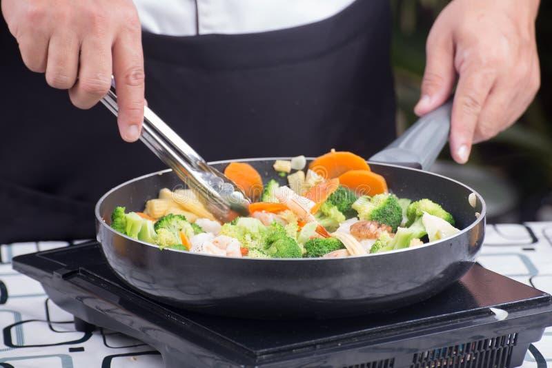 Ο αρχιμάγειρας ανακατώνει το λαχανικό τηγανητών στοκ εικόνα