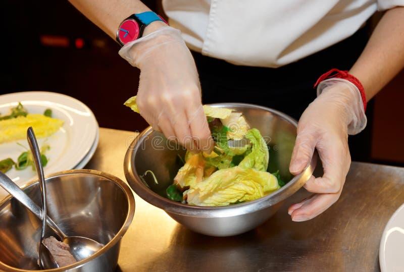 Ο αρχιμάγειρας αναμιγνύει τη σαλάτα στην επαγγελματική κουζίνα στοκ εικόνες