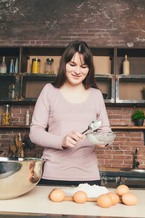 Ο αρχιμάγειρας γυναικών κοσκινίζει το αλεύρι, ζυμώνει τη ζύμη Έννοια αρτοποιείων ή ψησίματος συστατικά αλευριού αυγών ζύμης στοκ φωτογραφίες