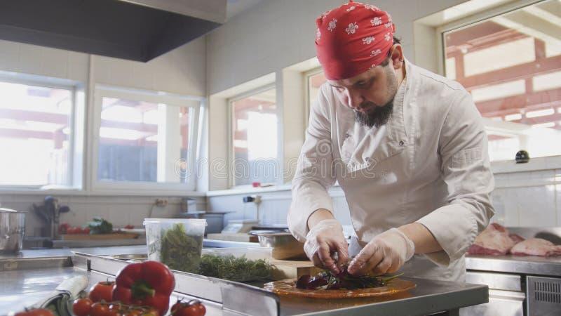 Ο αρχιμάγειρας εξυπηρετεί τη σαλάτα με την τοποθέτηση των συστατικών σε ένα πιάτο στοκ φωτογραφίες με δικαίωμα ελεύθερης χρήσης