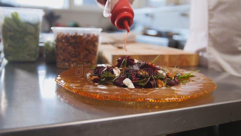 Ο αρχιμάγειρας εξυπηρετεί τη σαλάτα προσθέτοντας τη σάλτσα, φρέσκα λαχανικά στο πρώτο πλάνο στοκ φωτογραφία