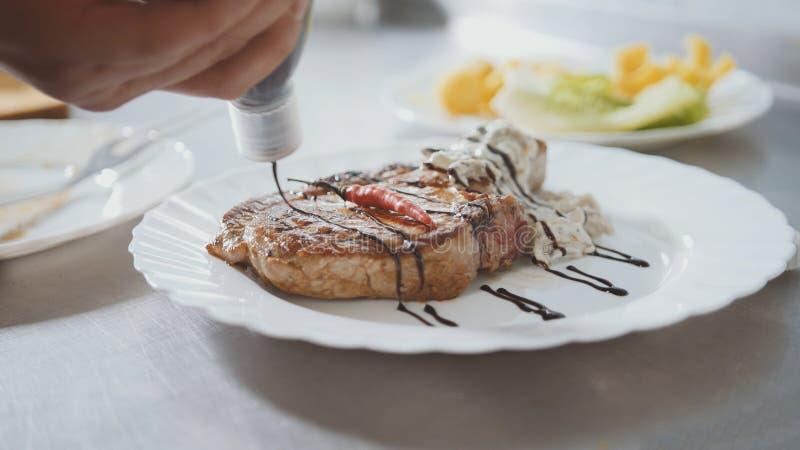 Ο αρχιμάγειρας εξυπηρετεί το κρέας στο πιάτο - κόκκινο πιπέρι και σάλτσα στοκ φωτογραφία με δικαίωμα ελεύθερης χρήσης