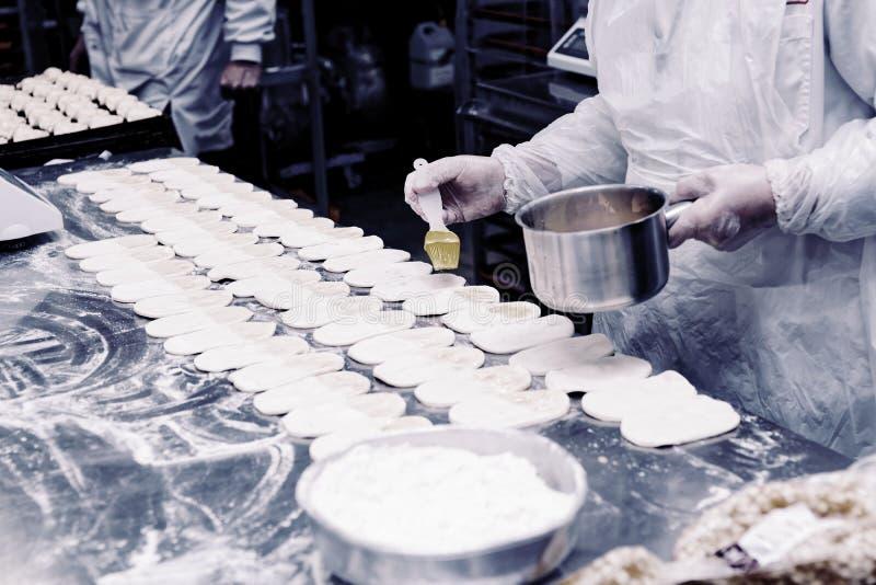 Ο αρχιμάγειρας ζύμης κάνει τα κουλούρια, που τονίζονται στοκ εικόνες