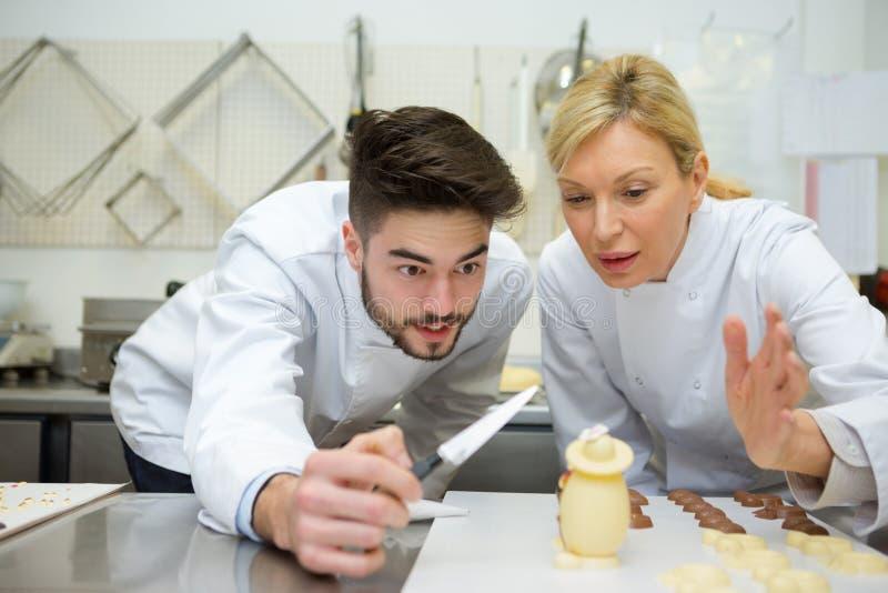 Ο αρχιμάγειρας και ο βοηθός προετοιμάζουν τα εύγευστα αυγά σοκολατών στην κουζίνα στοκ εικόνα με δικαίωμα ελεύθερης χρήσης
