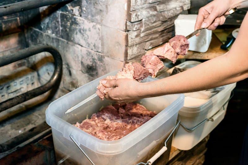 Ο αρχιμάγειρας κοριτσιών μαγειρεύει το κρέας με το χέρι τη σχάρα στοκ εικόνες