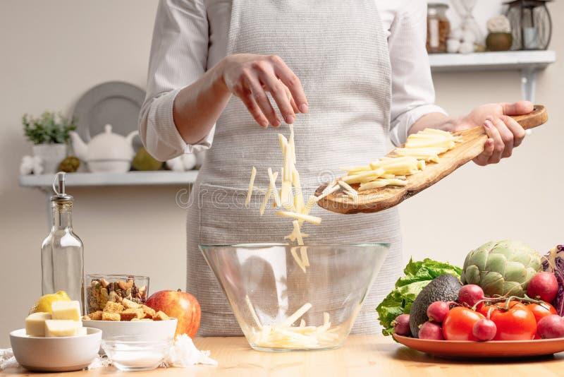 Ο αρχιμάγειρας μαγειρεύει, τεμαχίζει ένα μήλο, ανακατώνει, στο στάδιο μιας χορτοφάγου σαλάτας με το χέρι του αρχιμάγειρα στο φως  στοκ εικόνες