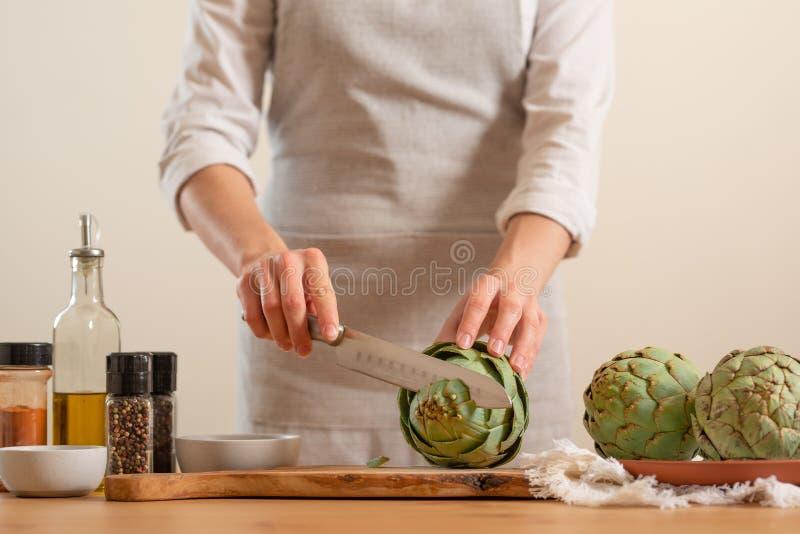 Ο αρχιμάγειρας μαγειρεύει την αγκινάρα Υ που τεμαχίζει την σε ένα ελαφρύ υπόβαθρο, έννοια μαγειρεύοντας τα νόστιμα και υγιή τρόφι στοκ εικόνες