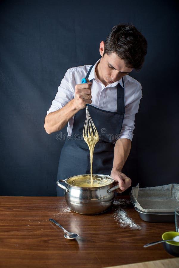 Ο αρχιμάγειρας νεαρών άνδρων στη μαύρη ποδιά προετοιμάζει τη ζύμη για το ψήσιμο του κέικ Έννοια των ατόμων που μαγειρεύουν τα επι στοκ εικόνες