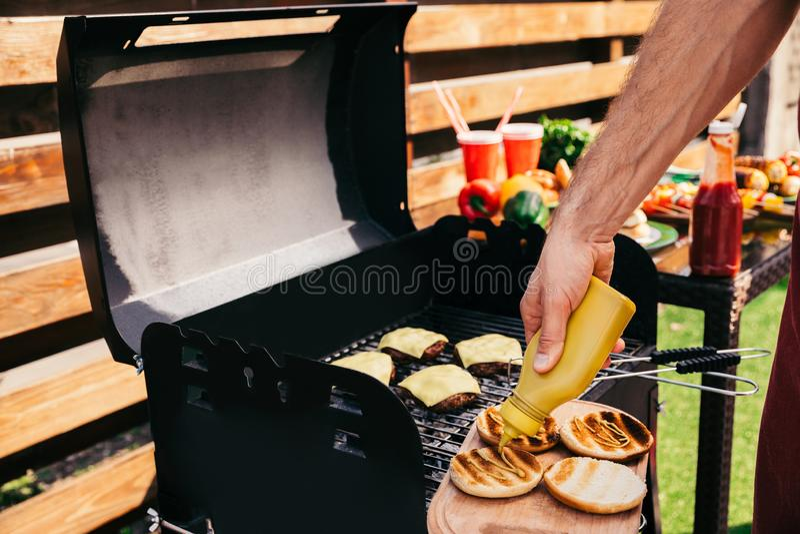 Ο αρχιμάγειρας που προσθέτει τη μουστάρδα στα burgers που ψήνεται στη σχάρα για ψήνει υπαίθρια στοκ φωτογραφία