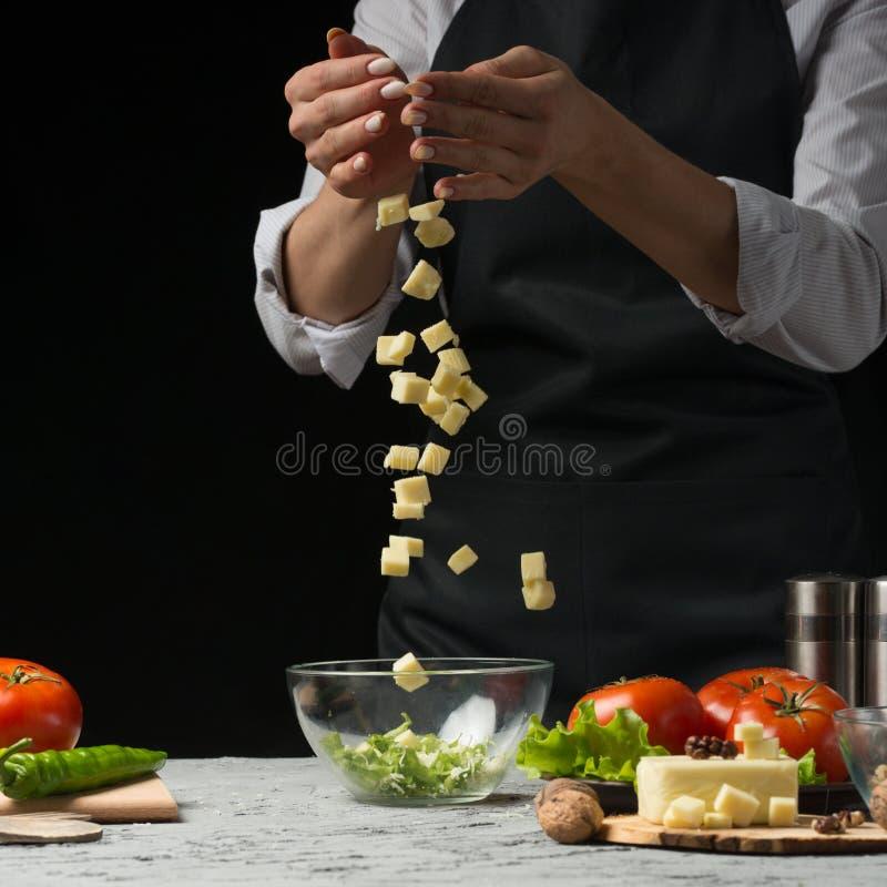 Ο αρχιμάγειρας προετοιμάζει μια σαλάτα, παγωμένο τυρί φέτας, μοτσαρέλα, σε ένα σκοτεινό υπόβαθρο με ένα κενό διάστημα για μια επι στοκ εικόνες με δικαίωμα ελεύθερης χρήσης