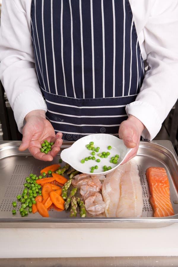 Download Ο αρχιμάγειρας προσθέτει τα μπιζέλια Στοκ Εικόνες - εικόνα από πρόσωπο, κουζίνα: 17055428