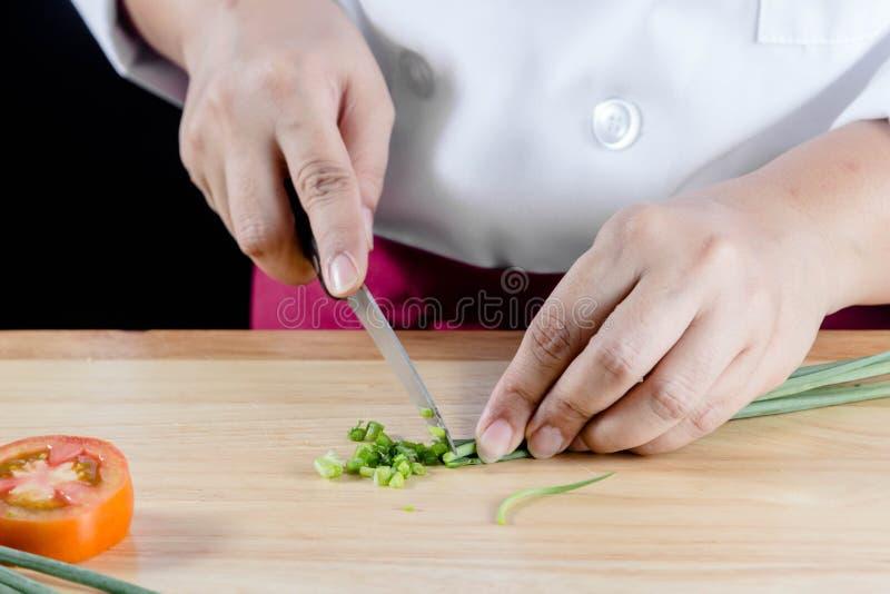 Ο αρχιμάγειρας τεμάχισε τα πράσινα κρεμμύδια στοκ εικόνες με δικαίωμα ελεύθερης χρήσης