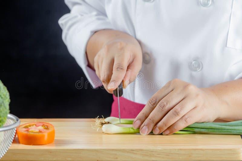 Ο αρχιμάγειρας τεμάχισε τα πράσινα κρεμμύδια στοκ εικόνα