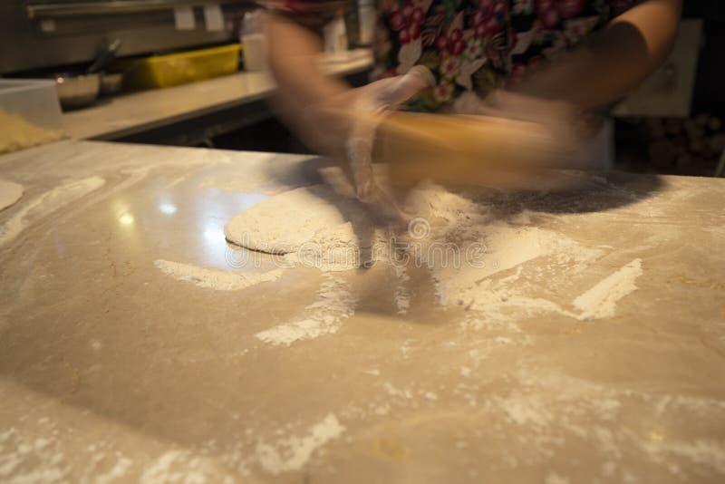 Ο αρχιμάγειρας της Ασίας χρησιμοποιεί μια καρφίτσα στην κατασκευή της ζύμης πιτσών στοκ εικόνες με δικαίωμα ελεύθερης χρήσης