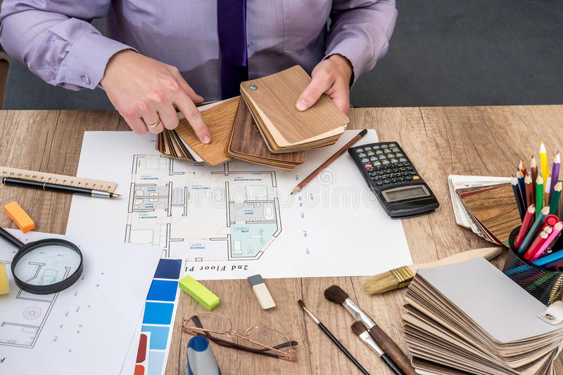Ο αρχιτέκτονας ατόμων σύρει ένα σχέδιο σπιτιών με την παλέτα χρώματος για τα έπιπλα, στοκ εικόνες