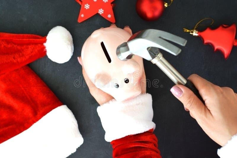 Ο αρωγός Santa's προετοιμάστηκε για τις υψηλές δαπάνες στο χρόνο Χριστουγέννων, με τη piggy τράπεζα και το σφυρί στο υπόβαθρο Χ στοκ εικόνα με δικαίωμα ελεύθερης χρήσης