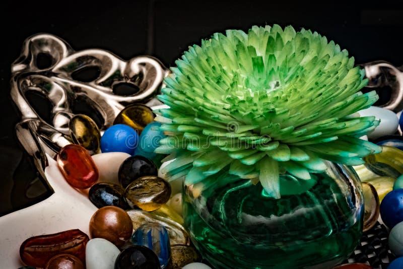 Ο αρωματικός εξαγνιστής αέρα στο γυαλί κυλά διακοσμητικά κομμάτια για το τραπεζάκι σαλονιού με τα ζωηρόχρωμα μάρμαρα στοκ φωτογραφία