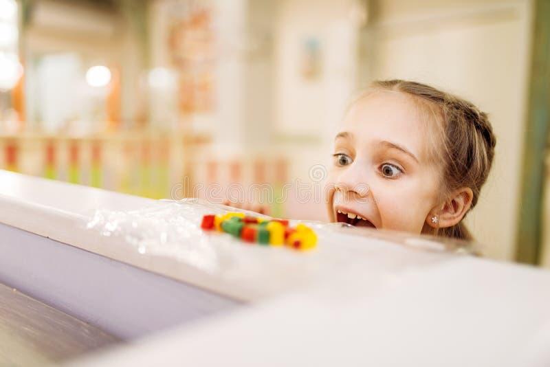 Ο ασήμαντος κλέφτης παίρνει το γλυκό από τον πίνακα στο κατάστημα καραμελών στοκ φωτογραφία