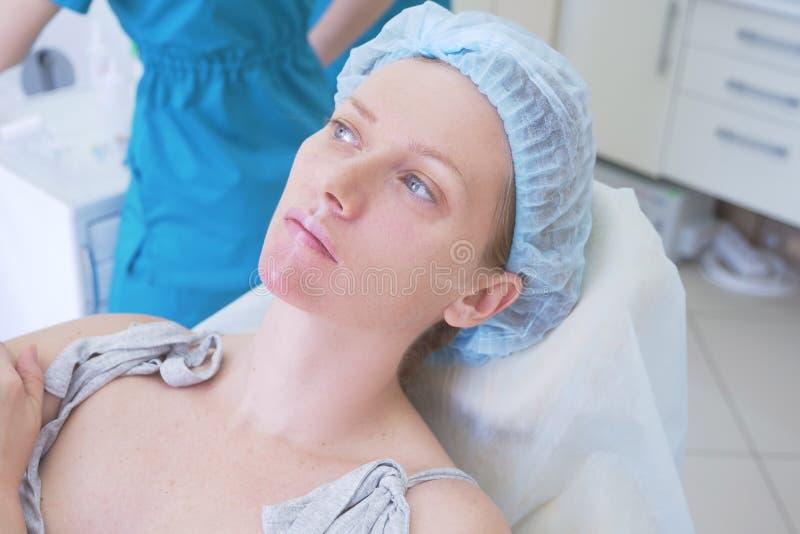 Ο ασθενής γυναικών σε ένα υγιεινό καπέλο αναμένει τη διαδικασία στο γραφείο γιατρών ` s Κινηματογράφηση σε πρώτο πλάνο 4K στοκ φωτογραφίες με δικαίωμα ελεύθερης χρήσης