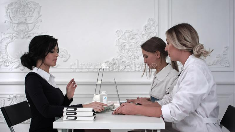 Ο ασθενής πληρώνει για τη θεραπεία στο γραφείο στοκ φωτογραφίες