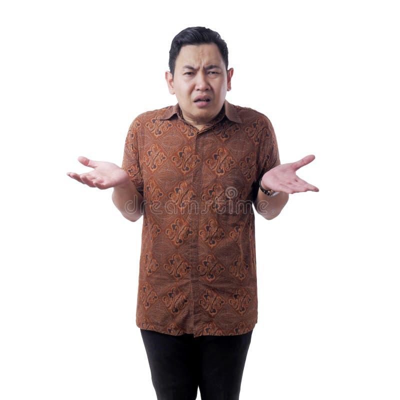 Ο Ασιάτης που φοράει μπατίκ πουκάμισο δείχνει αδιάφορη χειρονομία στοκ εικόνες με δικαίωμα ελεύθερης χρήσης