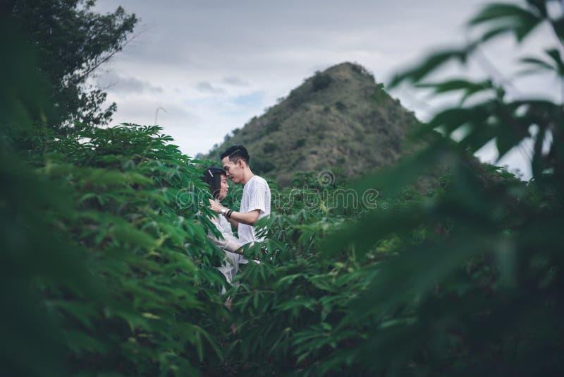 """Ο Ασιάτης σύζυγος φιλάει την έγκυο σύζυγό Ï""""Î¿Ï… με τα μάτια Ï""""Î¿Ï… κλειστά ÏƒÏ στοκ εικόνα"""