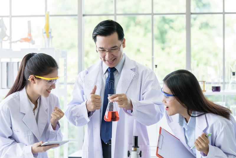 Ο ασιατικός ανώτερος επιστήμονας έχει να διδάξει το νέο επιστήμονα σπουδαστών σε ένα εργαστήριο στοκ εικόνες