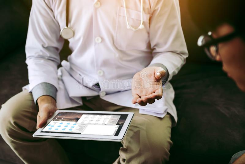 Ο ασιατικός γιατρός επισκέφτηκε τον ασθενή στο σπίτι χρησιμοποιώντας την ταμπλέτα εξηγώντας τον υπομονετικό όρο και το αποτέλεσμα στοκ φωτογραφία με δικαίωμα ελεύθερης χρήσης