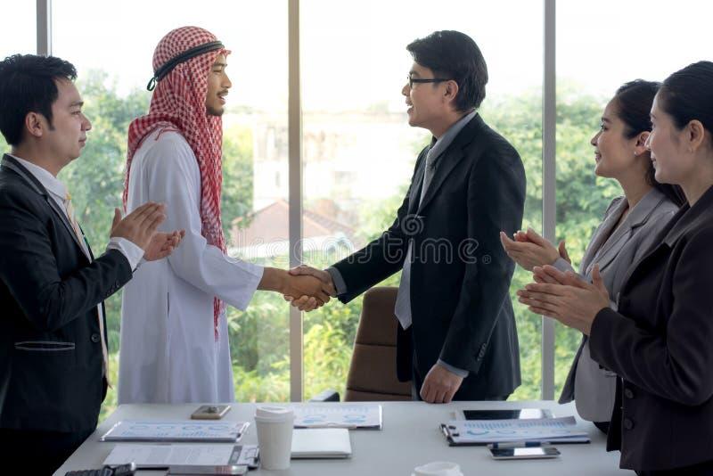 Ο ασιατικός επιχειρηματίας και η αραβική επιτυχία επιχειρηματιών στα χέρια τινάγματος διαπραγμάτευσης με τους επιχειρηματίες χτυπ στοκ φωτογραφία με δικαίωμα ελεύθερης χρήσης