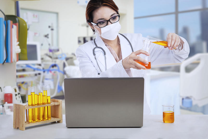 Ο ασιατικός θηλυκός γιατρός αναλύει το υγρό στην κλινική στοκ φωτογραφία με δικαίωμα ελεύθερης χρήσης