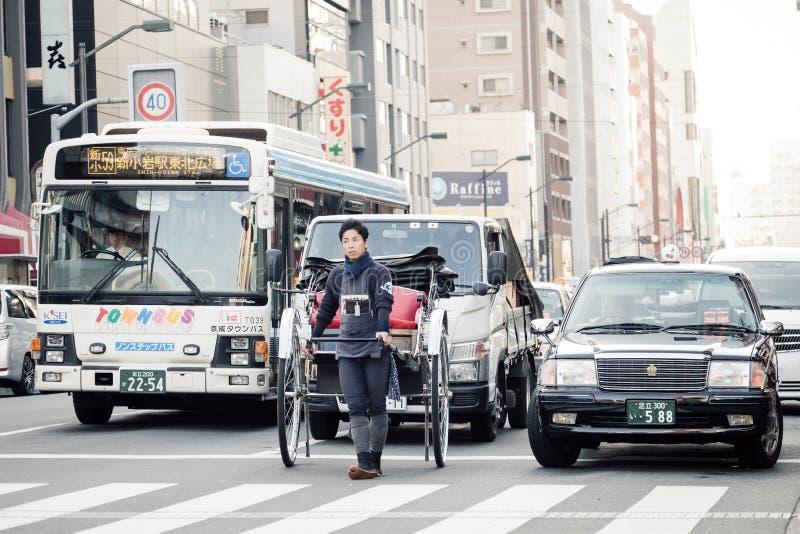 Ο ασιατικός νεαρός άνδρας τραβά ένα richshaw, δίτροχο άτομο-τροφοδοτημένο οχήματα κάρρο στο Τόκιο, Ιαπωνία στοκ φωτογραφία με δικαίωμα ελεύθερης χρήσης