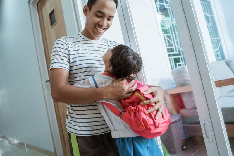 Ο ασιατικός σπουδαστής παιδικών σταθμών αγκαλιάζει τον μπαμπά της ενώπιον του σχολείου στοκ εικόνα