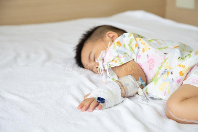 Ο ασιατικός ύπνος αγοράκι στο κρεβάτι με την έγχυση έθεσε στο τμήμα παιδιών στο νοσοκομείο στοκ φωτογραφία με δικαίωμα ελεύθερης χρήσης