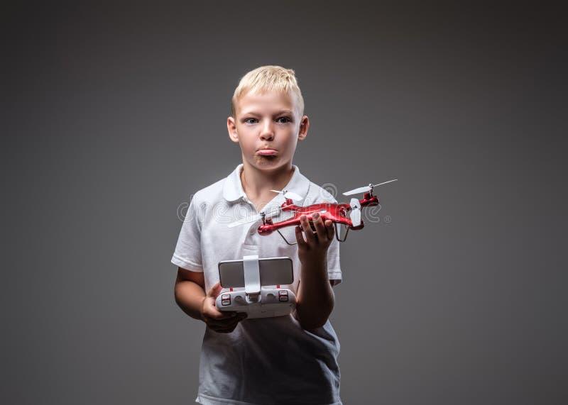 Ο αστείος μπόξερ αγοριών με την ξανθή τρίχα που ντύνεται σε μια άσπρη μπλούζα κρατά ένα quadcopter και έναν έλεγχο μακρινούς στοκ εικόνα με δικαίωμα ελεύθερης χρήσης