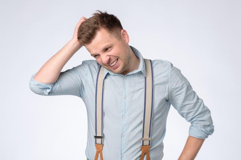 Ο αστείος νεαρός άνδρας κρατά το κεφάλι του που ξεχνιέται υπό εξέταση κάτι στοκ φωτογραφίες