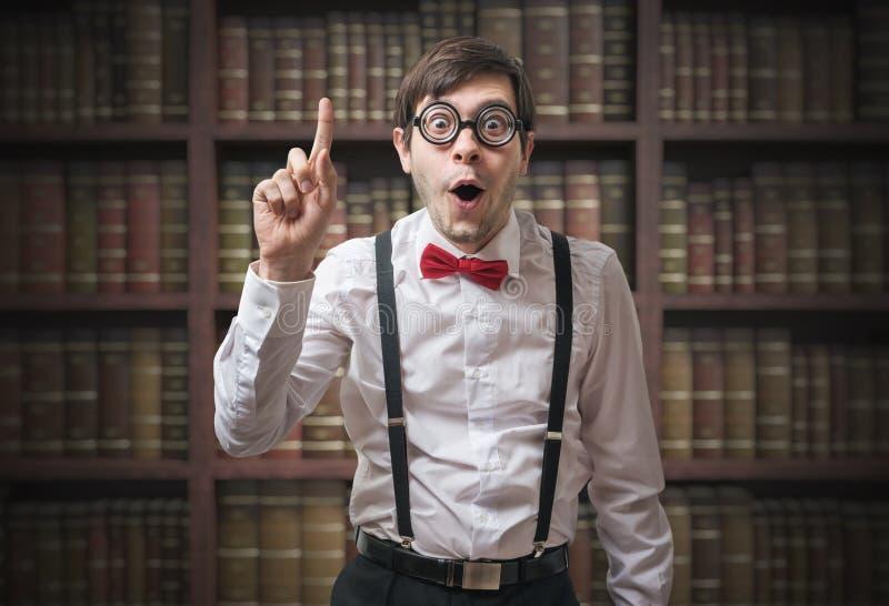 Ο αστείος νεαρός άνδρας nerd με το δάχτυλο έχει επάνω μια ιδέα στοκ εικόνα