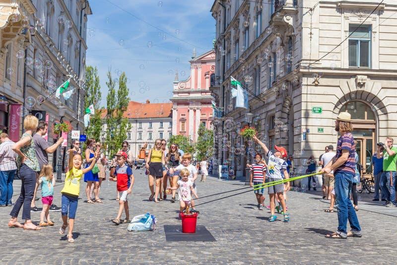 Ο αστικός καλλιτέχνης την ώρα της παράστασης οδών μια φυσαλίδα σαπουνιών παρουσιάζει για τα παιδιά στο μεσαιωνικό κέντρο πόλεων τ στοκ εικόνα με δικαίωμα ελεύθερης χρήσης
