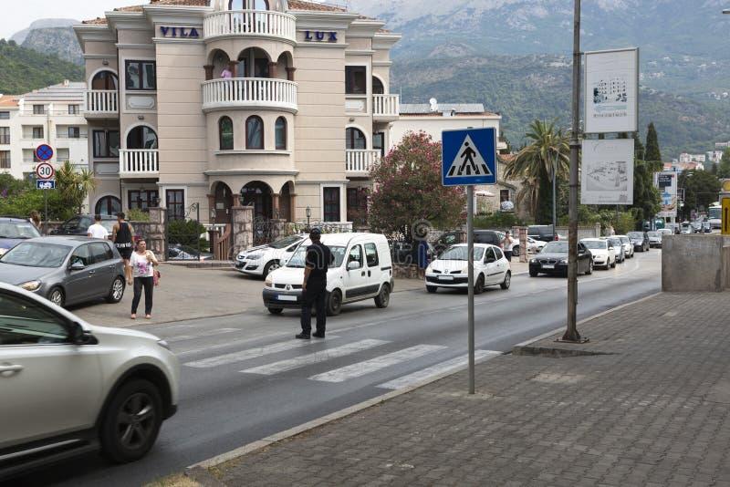Ο αστυνομικός κατευθύνει την κυκλοφορία στο για τους πεζούς πέρασμα Budva, Μαυροβούνιο στοκ φωτογραφία