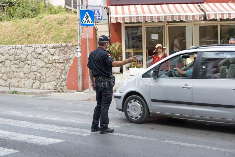 Ο αστυνομικός κατευθύνει την κυκλοφορία στο για τους πεζούς πέρασμα Budva, Μαυροβούνιο στοκ εικόνες