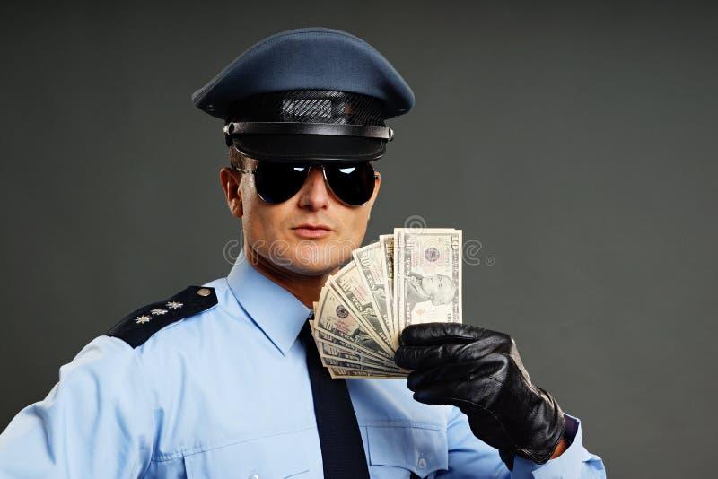 Ο αστυνομικός παρουσιάζει χρήματα στοκ εικόνα με δικαίωμα ελεύθερης χρήσης