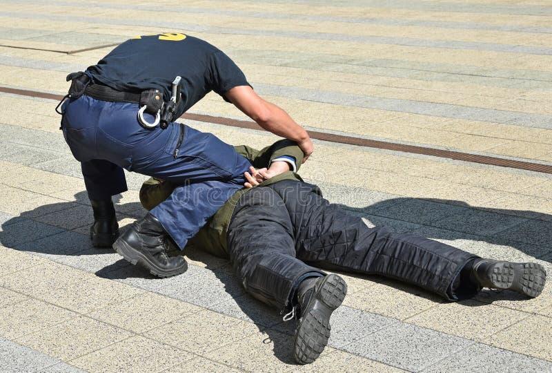 Ο αστυνομικός συλλαμβάνει έναν εγκληματία στην οδό στοκ φωτογραφίες