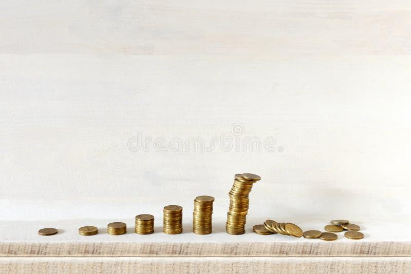 Ο αυξάνομαι τις στήλες νομισμάτων, η μεγαλύτερη πέφτει, όλες στο ξύλινο υπόβαθρο Μην κρατήστε όλα τα αυγά σας σε ένα καλάθι στοκ φωτογραφία με δικαίωμα ελεύθερης χρήσης