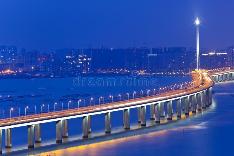 Ο αυτοκινητόδρομος στη νύχτα με τα αυτοκίνητα ανάβει στη σύγχρονη πόλη στοκ εικόνα
