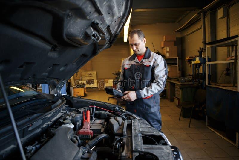 ο αυτόματος μηχανικός χρησιμοποιεί ένα βολτόμετρο πολυμέτρων για να ελέγξει το επίπεδο τάσης σε μια μπαταρία αυτοκινήτων στοκ φωτογραφία με δικαίωμα ελεύθερης χρήσης