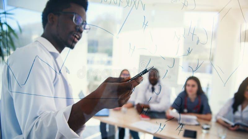 Ο αφρικανικός καθηγητής στην ιατρική διάσκεψη στη σύγχρονη κλινική διδάσκει τους σπουδαστές του Γιατρός που γράφει σε μερικούς τύ στοκ εικόνες