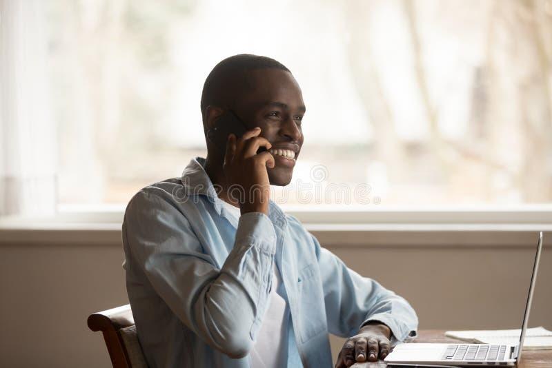 Ο αφρικανικός τύπος κάθεται στον πίνακα κοντά στη συζήτηση υπολογιστών στο smartphone στοκ φωτογραφίες με δικαίωμα ελεύθερης χρήσης